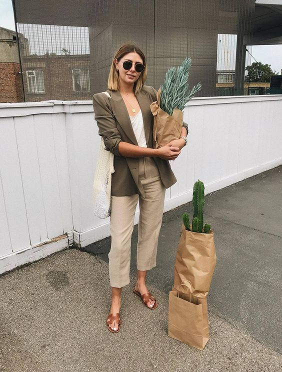 grey linen trousers, a white top, a green linen blazer, brown slippers, a neutral tote