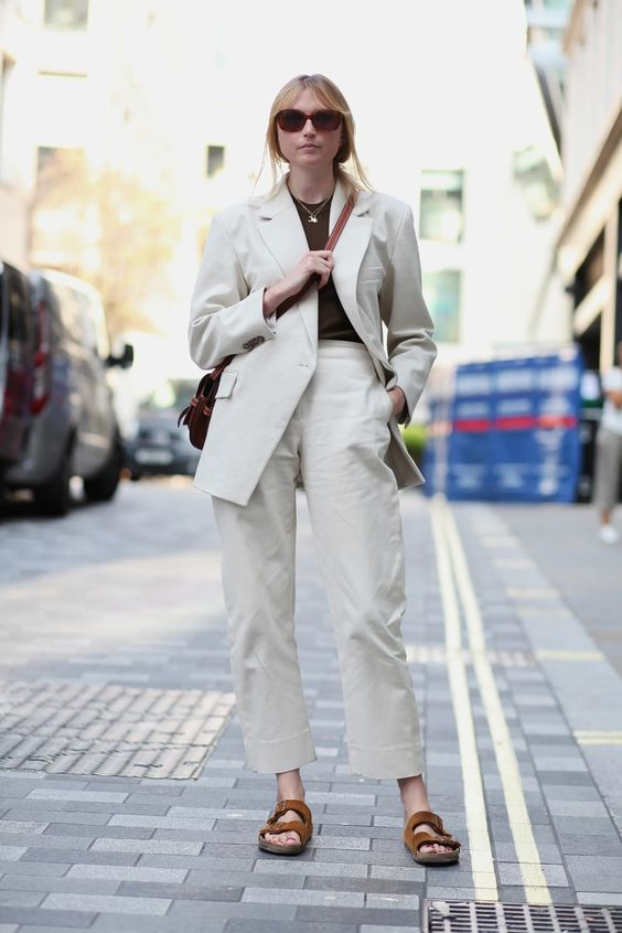 neutral linen pants and an oversized blazer, a rust-colored top, brown dad sandals and a brown bag for a super elegant look