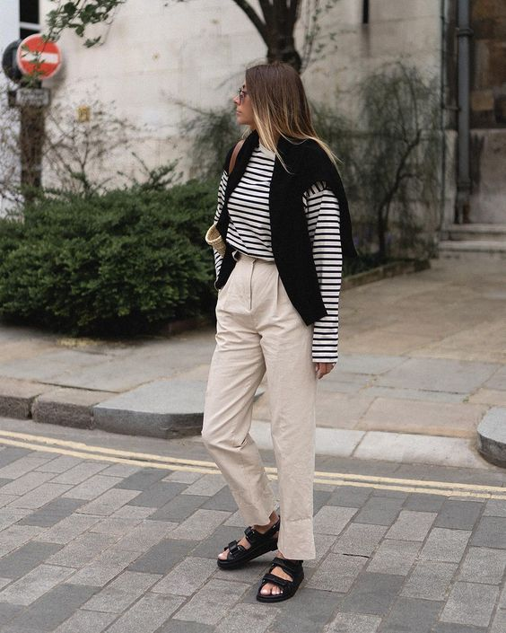 neutral trousers, a striped long sleeve shirt, black dad sandals, a black jumper in case it gets colder compose a casual work look