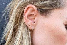 stacked ear piercings including lobe, orbital, helix and forward helix ones with delicate gold earrings