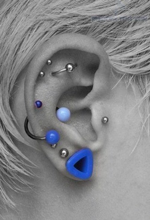 stacked earing piercings including a flat orbital, tragus, several helix and lobe piercings and super bold jewelry
