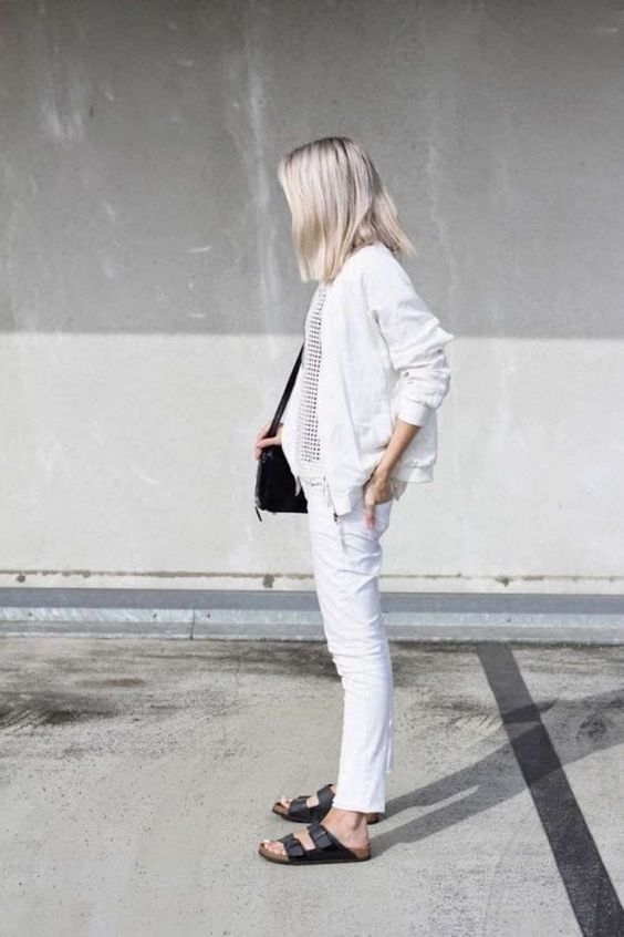 white jeans, a white bomber jacket, black birkenstocks, a printed top and a black bag for a chic summer work look