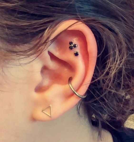 a lovely modern look with a double flat piercing, a conch and a lobe is a cool idea that looks non-typical and chic