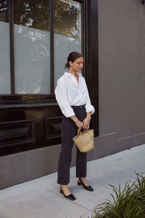 a white oversized shirt, black button up straight leg jeans, black slingbacks and a straw bag for a casual fall look