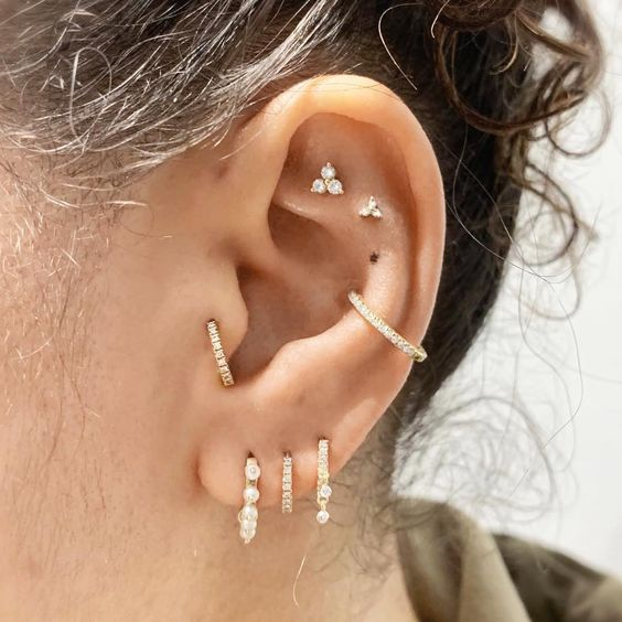 bold styling with a double flat, a conch, a triple lobe and a tragus piercing is a very cool and fresh idea to rock