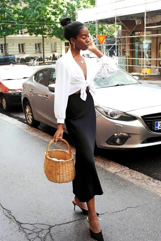 a black slip midi skirt, a white tied up shirt, black heeled mules, a basket bag for a romantic outfit