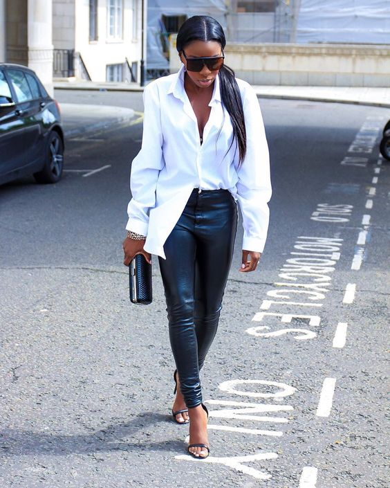 a chic outfit with a white oversized shirt, black leggings, black heels and a clutch looks very edgy