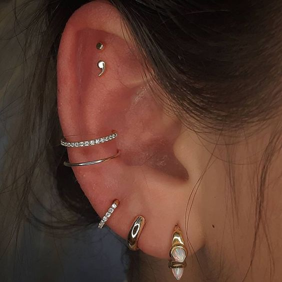 elegant ear styling with a triple lobe piercing, a double conch and a double flat one, with chic shiny hoops and studs