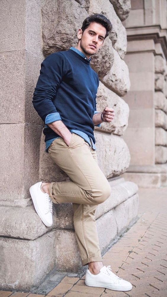 a simple and comfy look with a blue shirt, a navy jumper over it, tan jeans, white sneakers is an easy idea