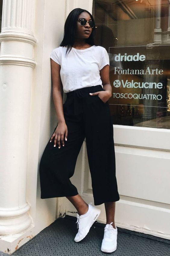 a white t-shirt, black culottes, white sneakers and sunglasses make up a cool and casual fall look