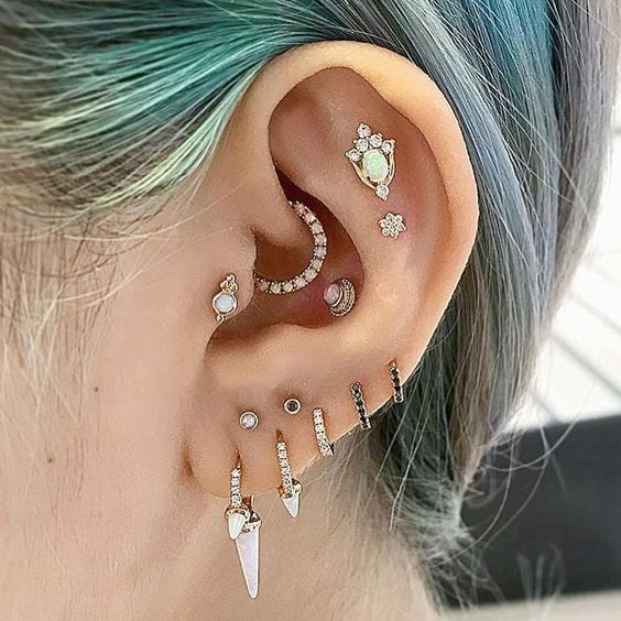 fabulous ear styling with multiple lobe, a double flat, a daith, conch and tragus piercing done with incredible hoop and stud earrings