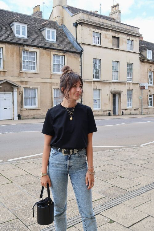 a timeless look with a black tee, layered necklaces, light blue jeans, an embellished belt, a black bucket bag