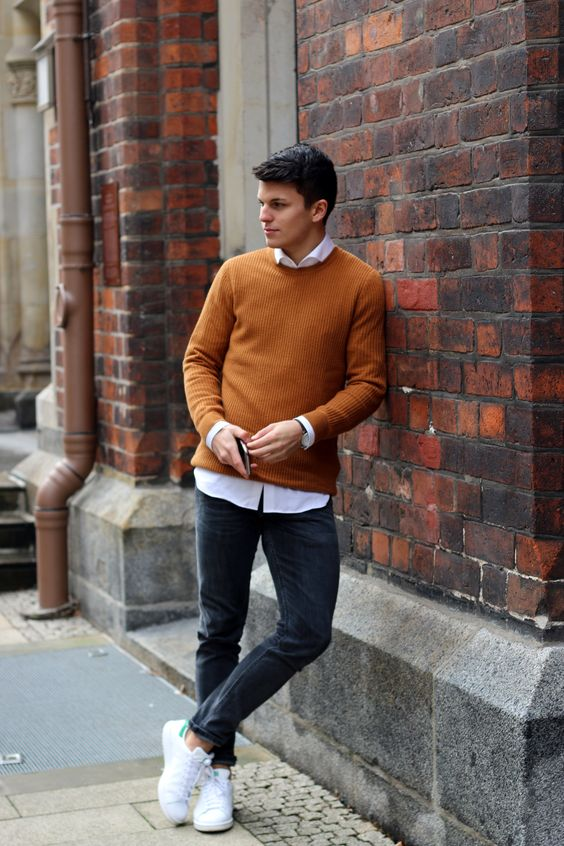 a bold fall outfit with a white shirt, a rust-colored jumper over it, black jeans and white sneakers