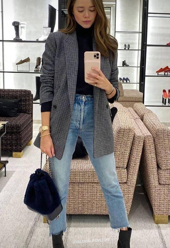 a black turtleneck, blue jeans, black boots, a grey plaid oversized blazer, a black bag for a casual look