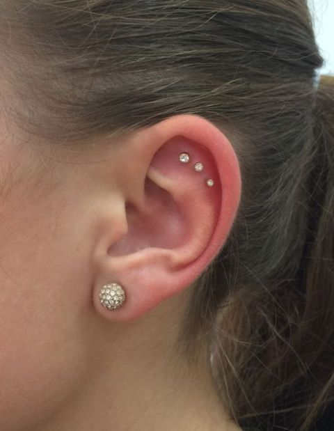 a cool triple flat piercing done with matching studs of mismatching sizes and a large stud earring in the lobe to finish the look