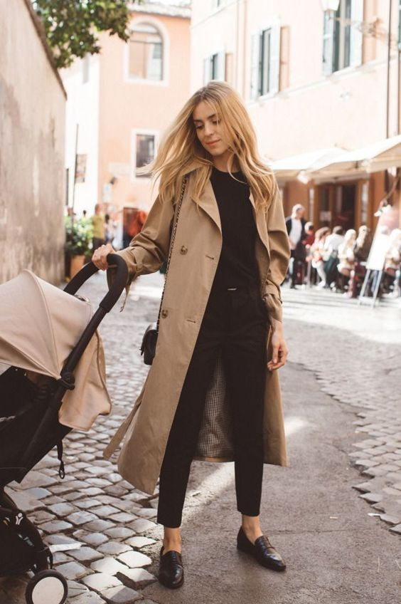 a black jumper, trousers, moccasins, a tan trench and a black bag for a timeless casual look
