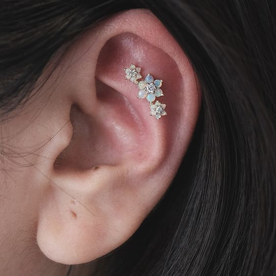 a gorgeous triple flat piercing done with matching opal studs of different sizes is a cool idea with a girlish feel