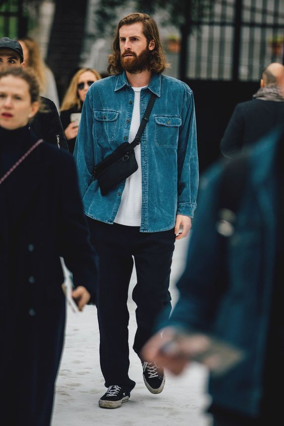 a white t-shirt, black trousers, black sneakers, a blue chambray shirt and a black waist bag for a fast and cool look