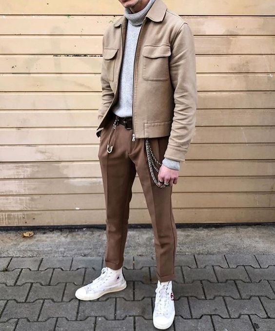 a bold and cool look with a grey turtleneck, brown pants, a brown shirt jacket, white sneakers and various accessories