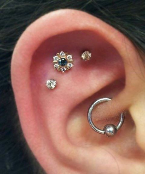 a triple flat piercing and a daith one styled with gorgeous gold studs and a simple hoop earring is a lovely idea