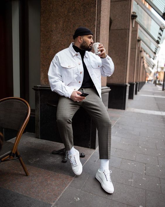 a stylish everyday look with a black turtleneck, grey trousers, a white denim jacket, white sneakers and a black beanie