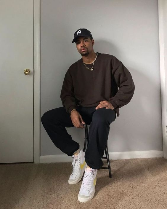a brown sweatshirt, black sweatpants, white sneakers and a black baseball cap for a comfortable and sporty look