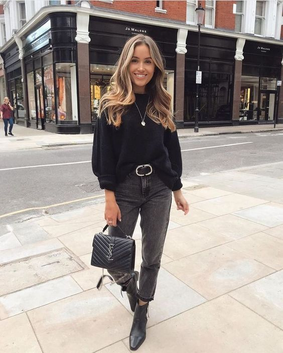 a monochromatic look with a black sweater, grey mom jeans, black booties, a black bag and a belt is chic