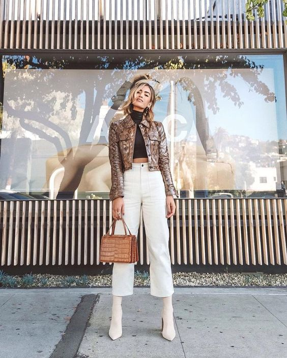 a stylish outfit with a black cropped turtleneck, white high waisted jeans, creamy booties, a metallic jacket and a tan bag