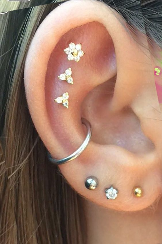 a triple lobe piercing plus a conch plus a triple flat piercing done with cool and chic studs and a hoop earring