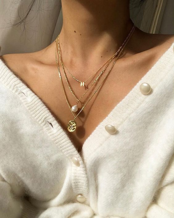 lovely layered necklaces with a monogram, a baroque pearl, a godl coin are amazing to highlight your V-neckline