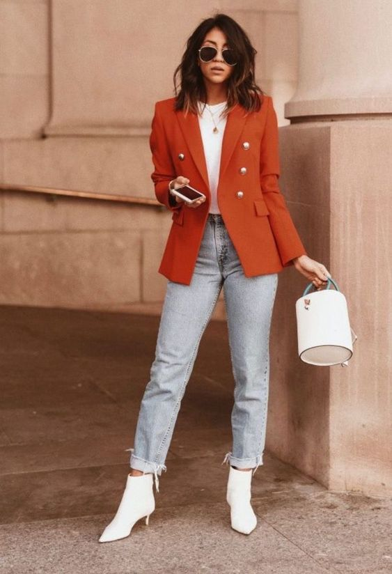a bright fall outfit with a white t-shirt, light blue jeans, white kitten heel booties, a rust blazer and a white bucket bag