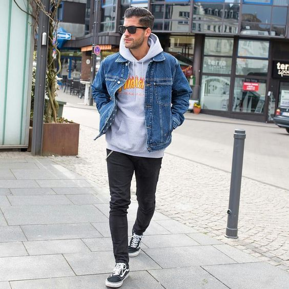 a comfy fall outfit with a grey hoodie, a blue denim jacket, black jeans, black sneakers always works and is very cozy