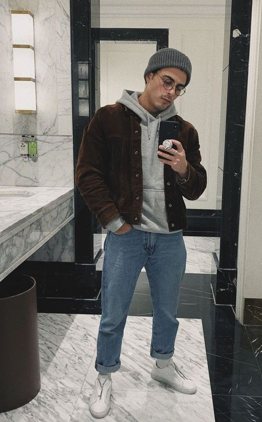 a grey hoodie, blue jeans, white sneakers, a brown corduroy jacket and a grey beanie for a comfy look