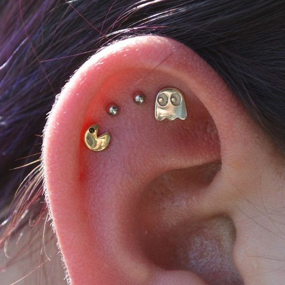funny and cheerful stacked flat piercings done with studs that show off a famous game is are very bold idea
