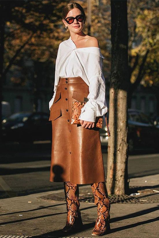 a trendy fall look with an oversized white shirt, an amber leather A-line midi, snakeskin print boots and a clutch