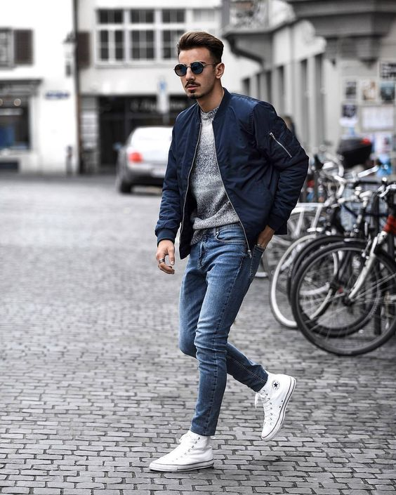 agrey jumper, blue jeans, white sneakers, a navy bomber jacket for a stylish and chic look
