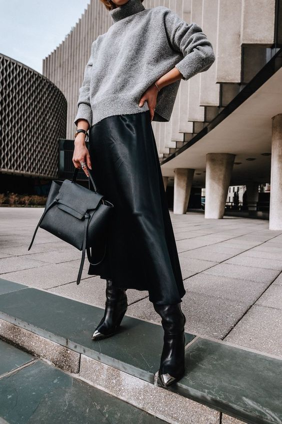 a grey sweater, a black slip midi skirt, black boots and a black bag compose a stylish look suitable for work