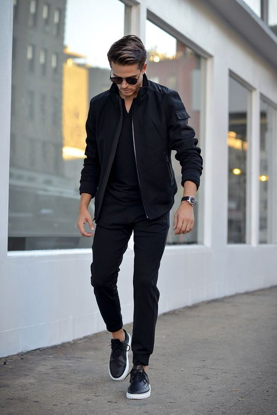 a total black look with a t-shirt, sweatpants, a bomber, sneakers and a watch is very chic and bold