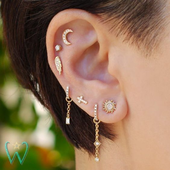 pretty earing styling with a multiple lobe piercing plus flat and helix ones done with creative chain hoops and shiny studs