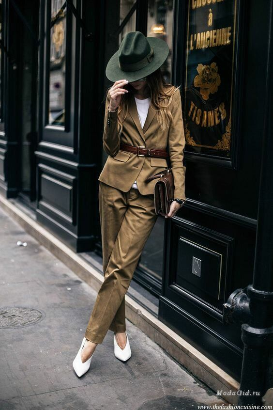 an elegant fall work look with a white tee, a tan pantsuit, a green hat, white shoes, a brown bag and a belt