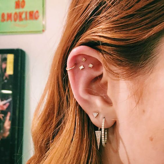 stylish stacked piercings - a double lobe piercing, a helix and a triple flat piercing, all done with rhinestone studs and hoops