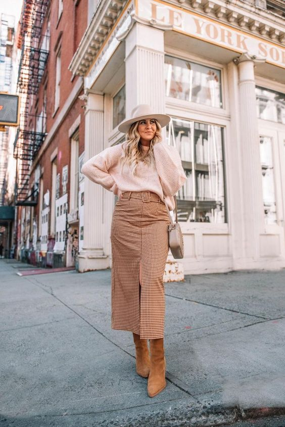 a neutral and cozy fall outfit with a blush sweater, a tan plaid front slit midi skirt, rust-colored boots, a grey bag and a hat
