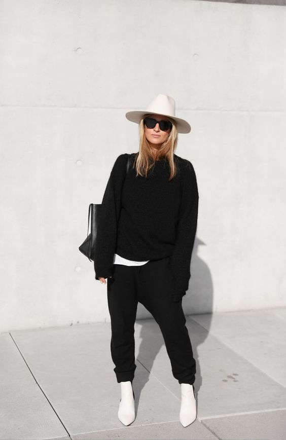 a relaxed fall outfit wiht a white tee, a black sweatshirt and sweatpants, white ankle boots, a hat and a black tote