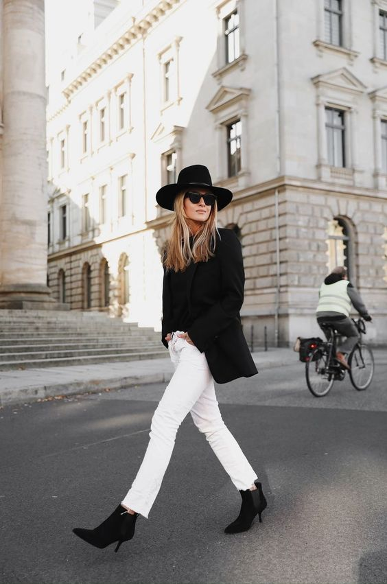 a monochromatic fall outfit wiht a black tee, a black blazer, white jeans, black ankle booties and a hat
