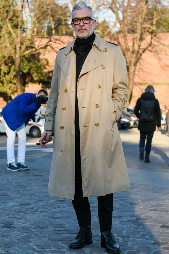 a black turtleneck, trousers, shoes and a tan trench coat for a stylish and chic look in the fall