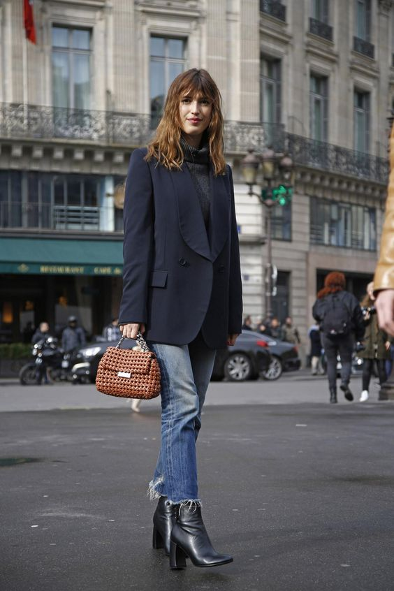 a Parisian-style fall look with a grey turtleneck, an oversized navy blazer, blue jeans, black boots and a catchy bag