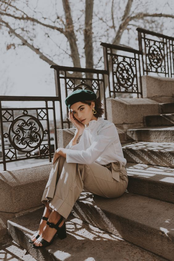 a Parisian chic outfit with a white shirt, tan high waisted trousers, black block heels and a black beret