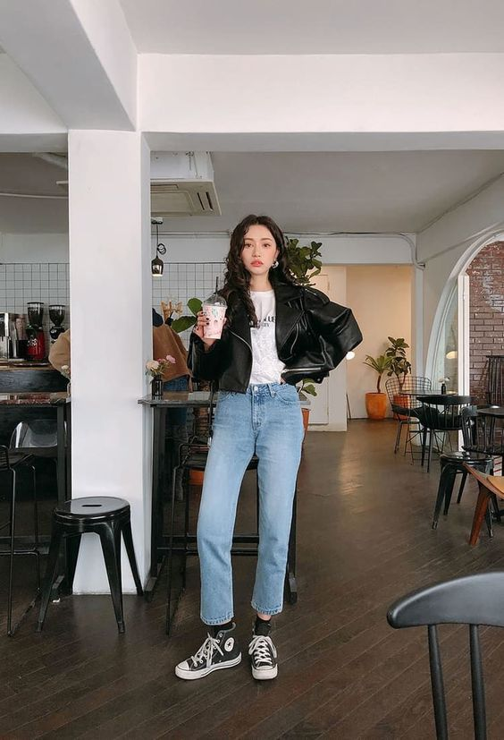 a basic look with a white printed tee, a black oversized leather jacket, blue jeans, black sneakers and socks