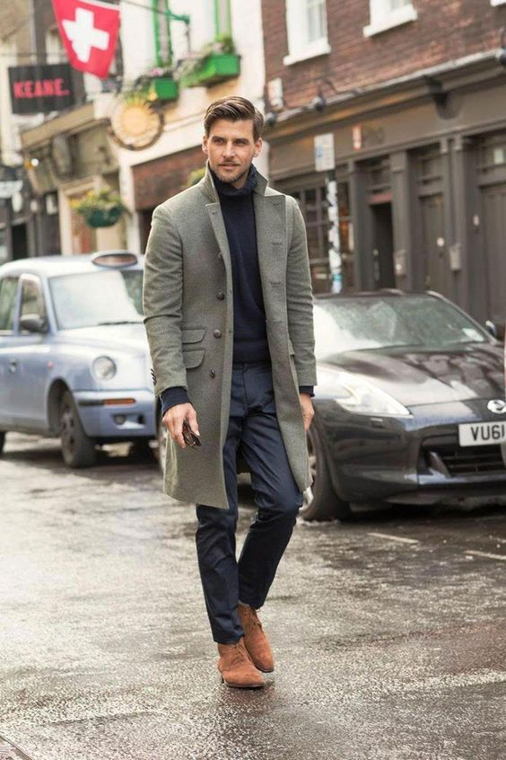 a navy jumper, navy trousers, a grey coat and rust-colored boots for a bold color accent