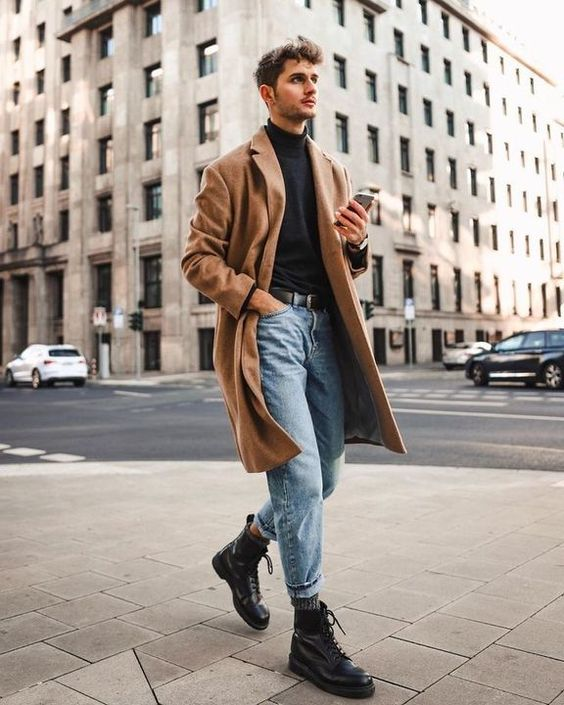 a black turtleneck, blue jeans, black boots, a tan coat and a black belt for a stylish and elegant fall look